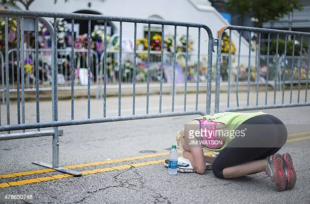 Kayleigh Dentici takes a moment to pray with her bible outside the Emanuel AME Church as funeral services for Rev and South Carolina State Sen...