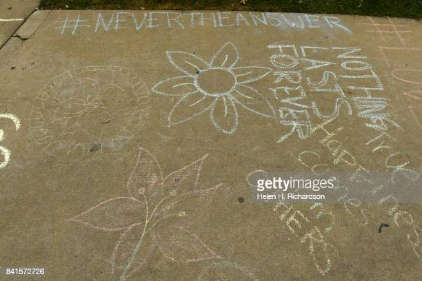 CENTENNITAL CO AUGUST Kayleigh Owen walks past some of the chalk art on the sidewalk that she helped create at Arapahoe High School for a student...