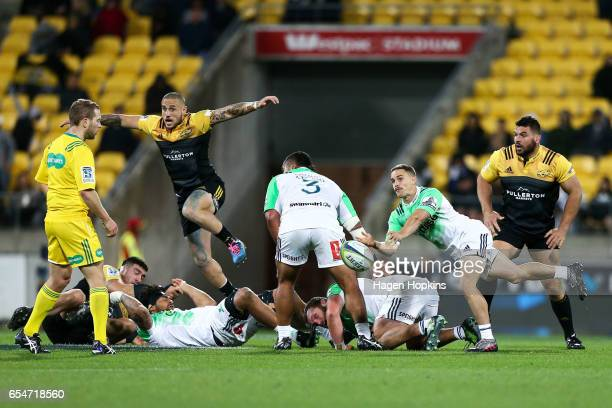 Kayne Hammington of the Highlanders passes while TJ Perenara of the Hurricanes gives chase during the round four Super Rugby match between the...