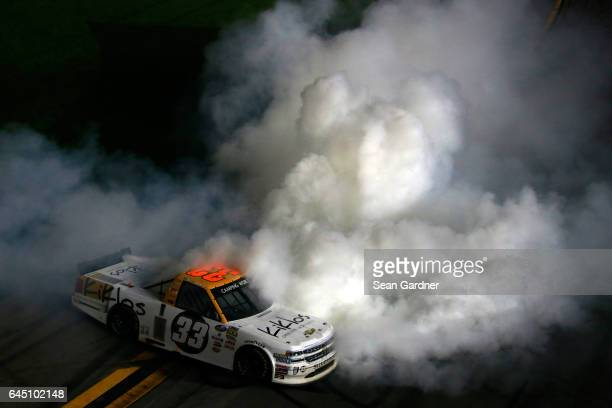 Kaz Grala driver of the KiklosGreekExtraVirginOliveOil Chevrolet celebrates with a burnout after winning the NASCAR Camping World Truck Series...