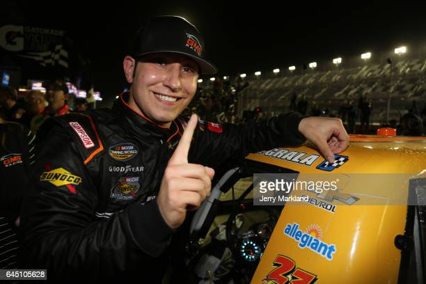Kaz Grala driver of the KiklosGreekExtraVirginOliveOil Chevrolet celebrates in Victory Lane by putting a winner's sticker on his truck during the...