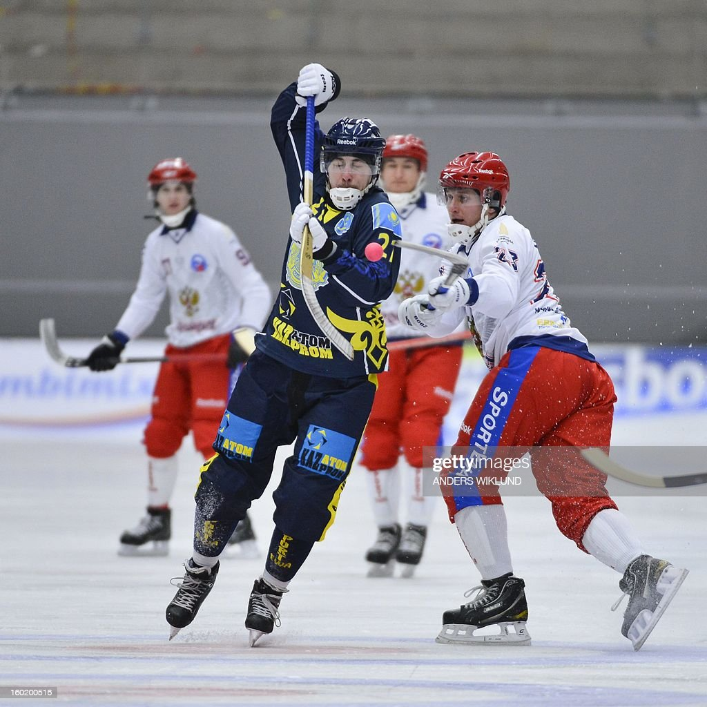 Kazahkstans Ryslan Galyutdinov (C) vies with Russia's Alexey Bushuev (R) during the Bandy World Championship match between Russia and Kazakhstan in Vanersborg, Sweden, on January 27, 2013. AFP PHOTO / ANDERS WIKLUND / SCANPIX SWEDEN SWEDEN OUT