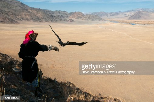 Kazakh eagle hunter letting golden eagle fly
