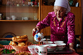Kazakh grandmother in national clothes pours tea