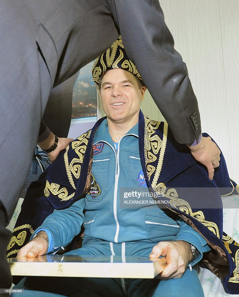 A Kazakh official hands over a traditional costume to US astronaut, Expedition 34 Commander Kevin Ford, at the airport of Kostanay, on March 16, 2013, after the landing in northern Kazakhstan. The three astronauts, Kevin Ford, Russian Soyuz Commander Oleg Novitskiy and Russian Flight Engineer Evgeny Tarelkin, returned safely to Earth from the International Space Station early today, aboard a Russian capsule which landed on the freezing Kazakhstan steppe, mission control said. AFP PHOTO / POOL / ALEXANDER NEMENOV
