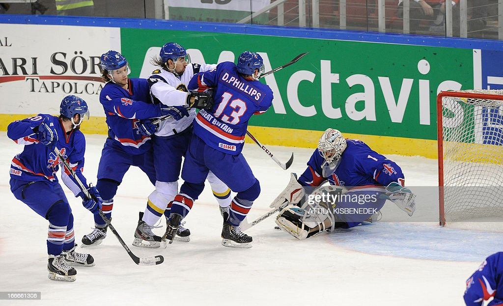 Kazakhstan Konstantin Romanov (C) vies with Great Britain's players during a 2013 IIHF Ice Hockey World Championship Division I Group A match between their teams in 'Papp Laszlo' Arena of Budapest on April 15, 2013.