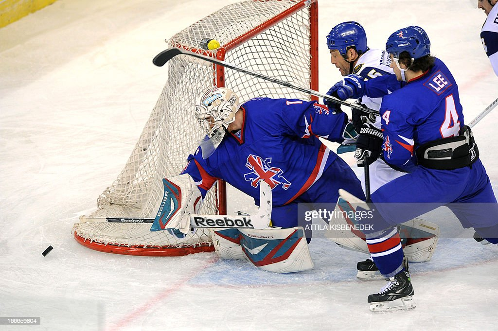 Kazakhstan's Alexei Troschinsky (C) fights for the ball with Great Britain's goalkeeper Stephen Murphy (L) and Stephen Lee (R) during a 2013 IIHF Ice Hockey World Championship Division I Group A match between their teams in 'Papp Laszlo' Arena of Budapest on April 15, 2013.