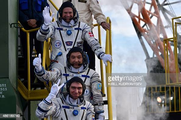 Kazakhstan's cosmonaut Aydyn Aimbetov Russian cosmonaut Sergei Volkov and Denmark's astronaut Andreas Mogensen from the European Space Agency wave as...