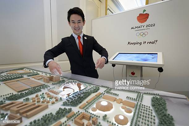 Kazakhstan's Denis Ten bronze medallist in figure skating at the 2014 Winter Olympics in Sochi shows a large scale model of the Olympic Park project...