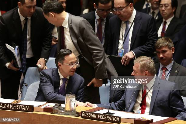 Kazakhstan's Foreign Minister Kairat Abdrakhmanov shakes hands with a Russian Foreign Ministry Official ahead of an open debate of the United Nations...