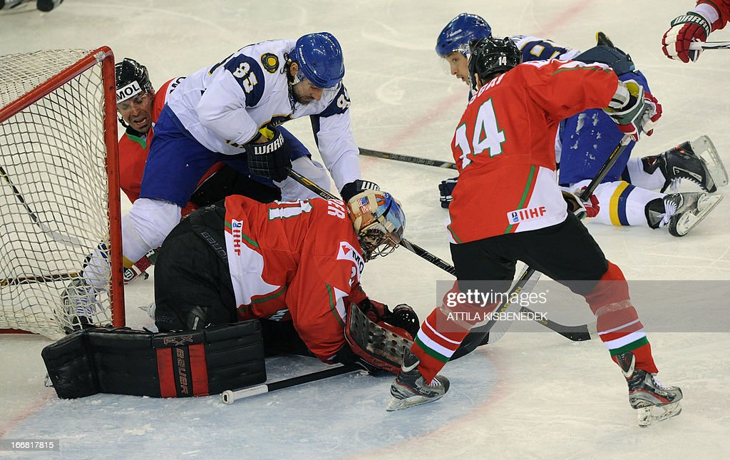 Kazakhstan's Konstantin Romanov (2L) vies with Hungary's Viktor Szelig (L), goalkeeper Levente Szuper (C) and Tamas Pozsgai (R) during the 2013 IIHF Ice Hockey World Championship Division I Group A match Kazakhstan vs Hungary in 'Papp Laszlo' Arena of Budapest on April 17, 2013.
