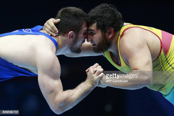 Kazakhstan's Mamed Ibragimov challenges Azerbaijan's Aslanbek Alborov during the men's freestyle wrestling 97kg category bronze medal final at the...