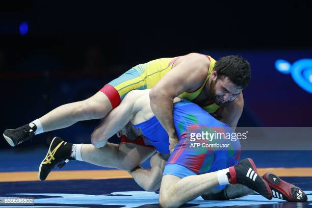 Kazakhstan's Mamed Ibragimov challenges Azerbaijan's Aslanbek Alborov during the men's freestyle wrestling 97kg category bronze medal final at the...