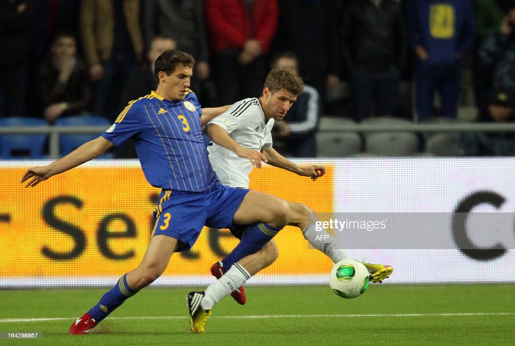 Kazakhstan's national football team players Valeri Korobkin (L) vies with Germany's national football team player Thomas Muller (R) during their 2014 World Cup qualifying football match in the Kazakh capital Astana, on March 22, 2013.