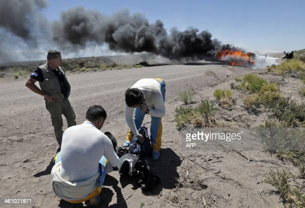 Kazakhstan's pilots Bauyrzhan Issabayev and Gabdulla Ashimov stand next to their burning car during the Dakar Rally 2014 Stage 2 from San Luis to San...
