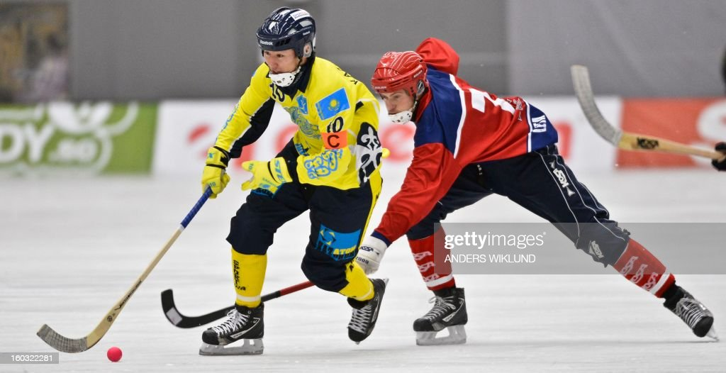 Kazakhstan's Rauan Issaliev (L) and Norway's Robin Cras (R) vie during the Bandy World Championship match between Kazakhstan and Norway in Vanersborg, Sweden, on January 29, 2013.