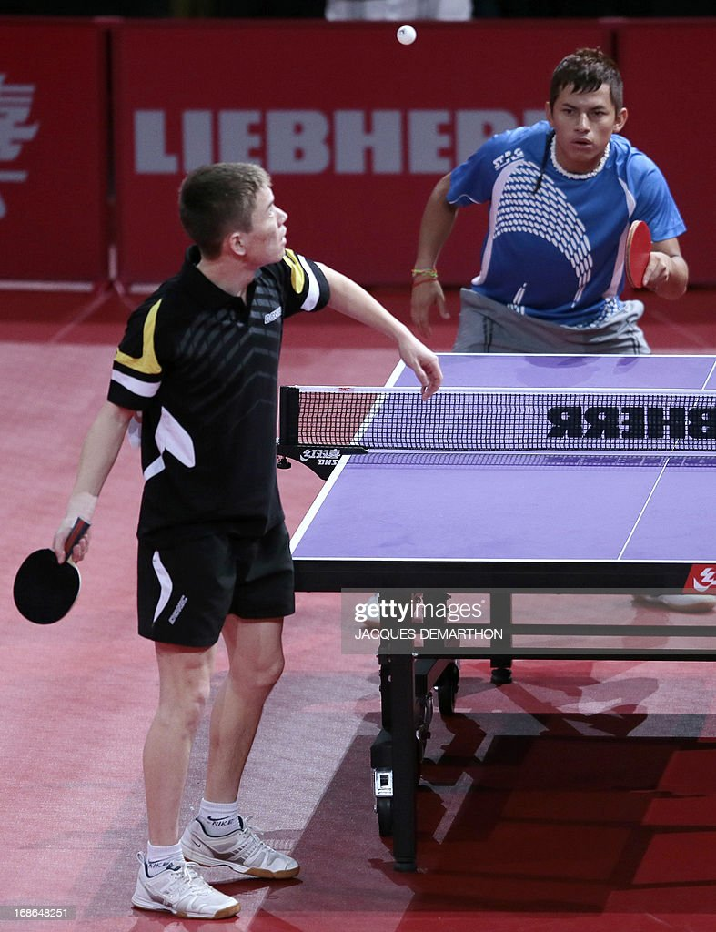Kazakhstan's Samat Beisenov (L) serves to Guatemala's Kevin Soto during a Men's Singles qualifications groups Table Tennis match at the World Table Tennis Championships on May 13, 2013 in Paris. AFP PHOTO / JACQUES DEMARTHON