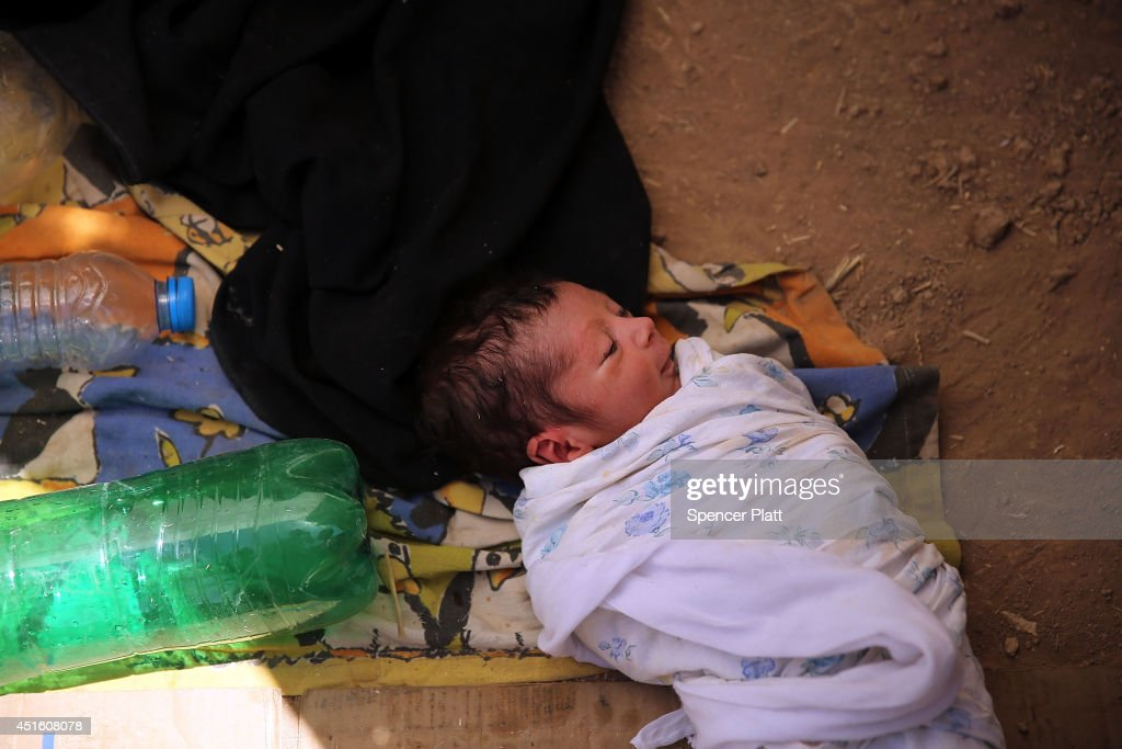 Kazem, a 13 day old girl who is sick, takes shelter under a sheet with her family as thousands of Iraqis who have fled recent fighting in the cities of Mosul and Tal Afar try to enter a temporary displacement camp but are blocked by Kurdish soldiers on July 2, 2014 in Khazair, Iraq. The families, many with small and sick children, have no shelter and little water and food. The displacement camp Khazair is now home to an estimated 1,500 internally displaced persons (IDP's) with the number rising daily. Tens of thousands of people have fled Iraq's second largest city of Mosul after it was overrun by ISIS (Islamic State of Iraq and Syria) militants. Many have been temporarily housed at various IDP camps around the region including the area close to Erbil, as they hope to enter the safety of the nearby Kurdish region.