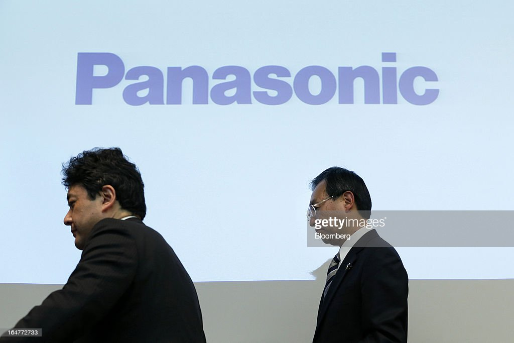 Kazuhiro Tsuga, president of Panasonic Corp., right, is escorted by a staff member as he leaves a news conference in Tokyo, Japan, on Thursday, March 28, 2013. Panasonic, Japan's second-biggest television maker, will sell part of its logistics unit and consider other asset sales as it targets operating profit of 350 billion yen ($3.7 billion) by the 2015 financial year. Photographer: Kiyoshi Ota/Bloomberg via Getty Images