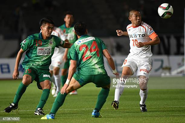 Kazuhisa Kawahara of Ehime FC passes the ball while Tsukasa Masuyama of FC Gifu watching during the JLeague second division match between FC Gifu and...
