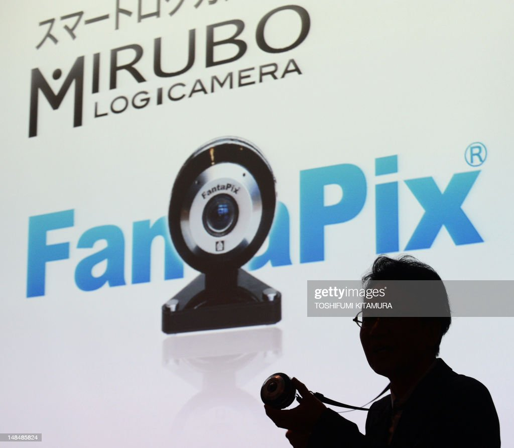 Kazuhisa Saito, CEO of Digital Act, Inc., is silhouetted as he speaks about the company's new product 'Mirubo' during a press preview in Tokyo on July 18, 2012. Mirubo is a next-generation super high-functioning smart log 1080-line high-definition motion picture camera that uses digital image compression technology called 'FantaPix' which was developed under a new concept to document life and business environments. AFP PHOTO / TOSHIFUMI KITAMURA