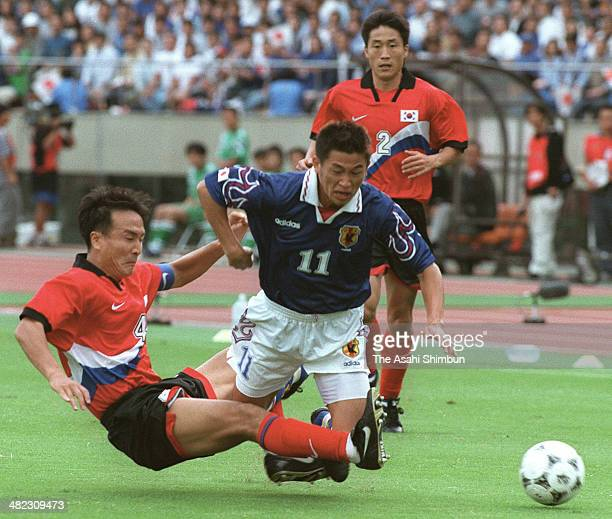 Kazuhoshi Miura of Japan is tackled by Choi YoungIl of South Korea during the France World Cup Asian Qualifier final round match between Japan and...