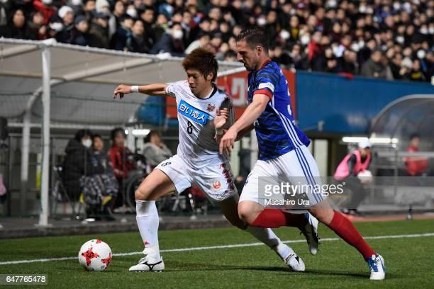 Kazuki Fukai of Consadole Sapporo and Milos Degenek of Yokohama FMarinos compete for the ball during the JLeague J1 match between Yokohama FMarinos...