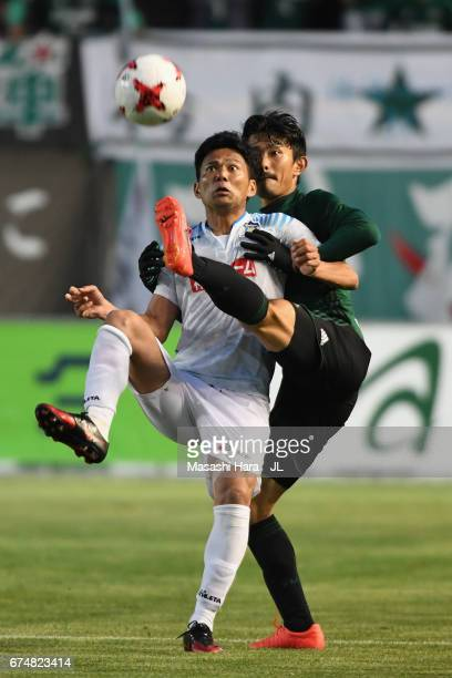 Kazuki Ganaha of Kamatamare Sanuki controls the ball under pressure of Keita Goto of Matsumoto Yamaga during the JLeague J2 match between Matsumoto...