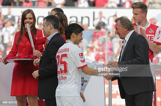 Kazuki Nagasawa of Cologne is congratulated by Deutsche Fussball Liga vice president Harald Strutz after winning the Second Bundesliga title at...