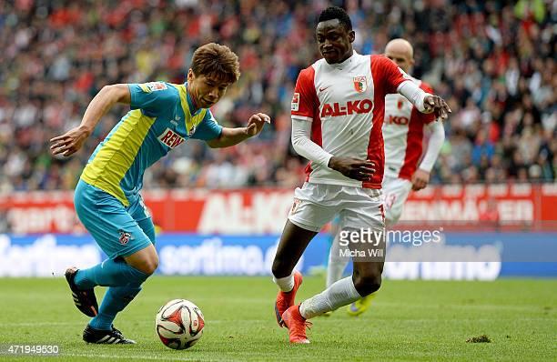 Kazuki Nagasawa of Koeln is challenged by Abdul Rahman Baba of Augsburg during the Bundesliga match between FC Augsburg and 1 FC Koeln at SGL Arena...