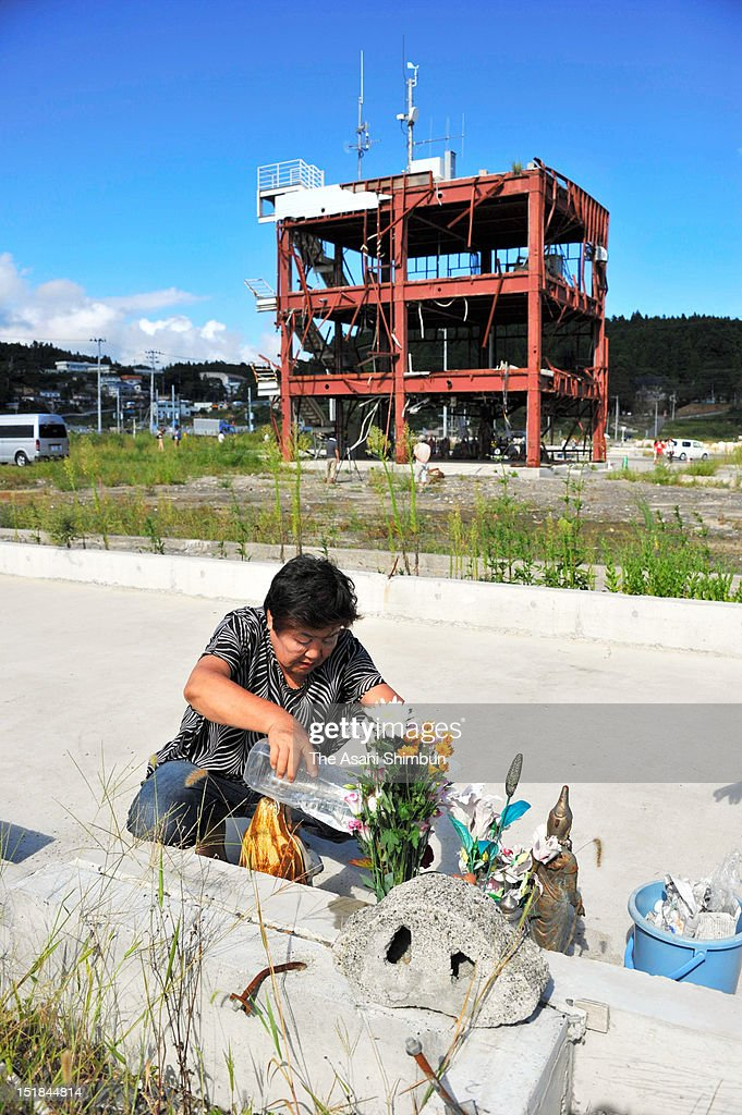Kazuko Yoshida, 69, offers a flower bunch to the place where she lost her sister-in-law by March 11 tsunami last year, near Minamisanriku Disaster Emergency Center on September 11, 2012 in Minamisanriku, Iwate, Japan. 18 months on, still 2,814 people are missing and 340,000 people are forced to live at temporary housing.