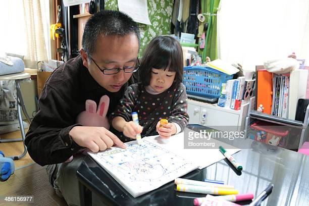 Kazunori Nagai helps his daughter Miku color in a book in their home in Tokyo Japan on Sunday March 2 2014 Prime Minister Shinzo Abe wants men to...