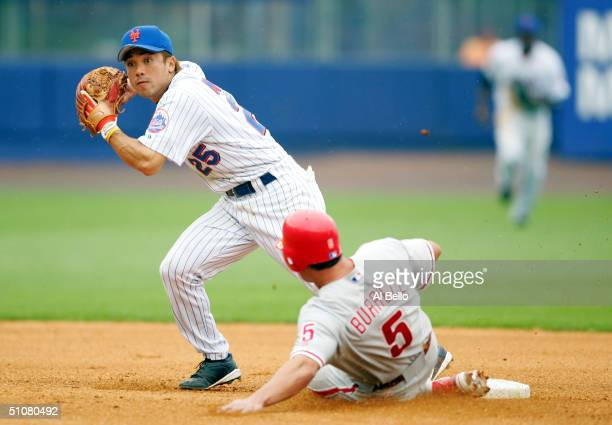 Kazuo Matsui of the New York Mets turns a double play as Pat Burrell of the Philadelphia Phillies slides into second base during their game on July...