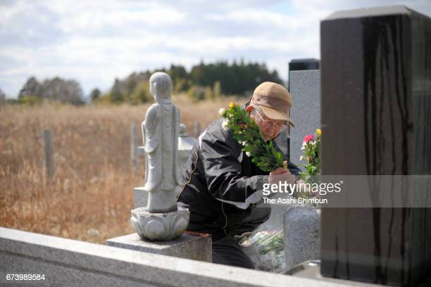 Kazuo Sato offers flowers at his ancestor's grave on the sixth anniversary of the Great East Japan Earthquake and following tsunami on March 11 2017...