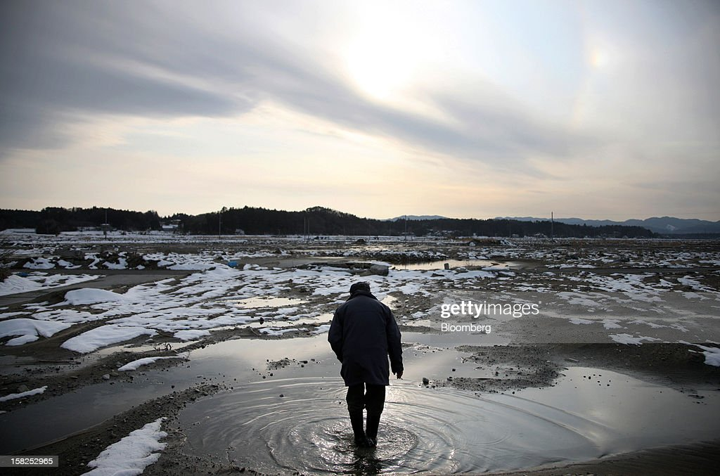 'BEST PHOTOS OF 2012' (): Kazushige Hayashi walks through puddles of water at the site of where his house stood before the March 11 earthquake and tsunami in Minamisoma City, Fukushima Prefecture, Japan, on Sunday, March 4, 2012. Japan marks the one-year anniversary of the earthquake and tsunami this month for the 15,845 dead and the 3,368 still missing. Photographer: Tomohiro Ohsumi/Bloomberg via Getty Images