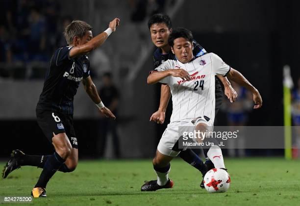 Kazuya Yamamura of Cerezo Osaka controls the ball under pressure of Yasuyuki Konno and Yosuke Ideguchi of Gamba Osaka during the JLeague J1 match...