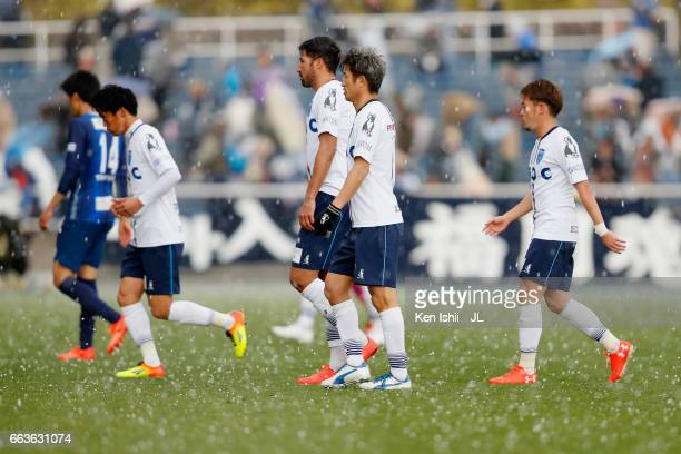 Kazuyoshi Miura of Yokohama FC and players leave the pitch as the game is suspended due to heavy hail during the JLeague J2 match between Avispa...