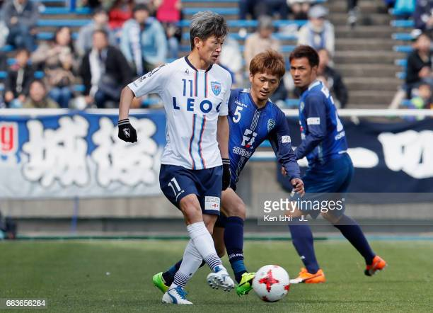 Kazuyoshi Miura of Yokohama FC controls the ball under pressure of Yuki Saneto of Avispa Fukuoka during the JLeague J2 match between Avispa Fukuoka...
