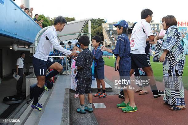 Kazuyoshi Miura of Yokohama FC greets children prior to the J League second division match between Yokohama FC and Avispa Fukuoka at Nippatsu...