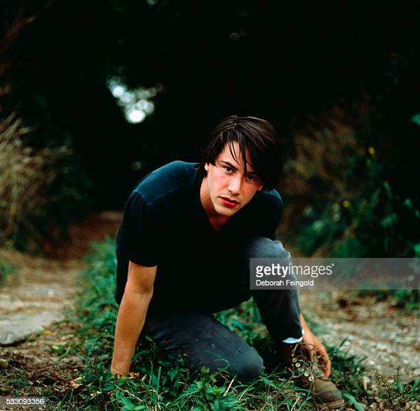 Keanu Reeves Crouching on Forest Path