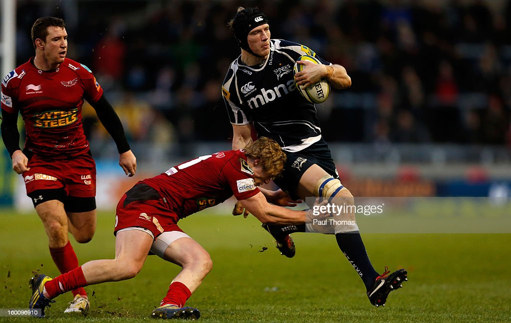 Kearnan Myall (R) of Sale Sharks is tackled by <a gi-track='captionPersonalityLinkClicked' href=/galleries/search?phrase=Aled+Davies+-+Jugador+de+la+uni%C3%B3n+de+rugby&family=editorial&specificpeople=15320798 ng-click='$event.stopPropagation()'>Aled Davies</a> of Scarlets during the LV= Cup match between Sale Sharks and Scarlets at Salford City Stadium on January 26, 2013 in Salford, England.