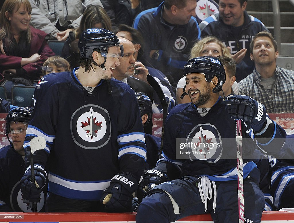 Keaton Ellerby #7 and Dustin Byfuglien #33 of the Winnipeg Jets share a laugh at the bench prior to overtime action against the Minnesota Wild at the MTS Centre on November 23, 2013 in Winnipeg, Manitoba, Canada. The Wild defeated the Jets 3-2 in the shootout.