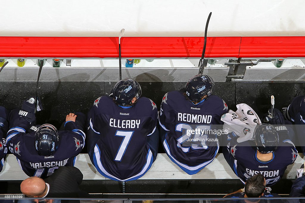 Keaton Ellerby #7 and Zach Redmond #25 of the Winnipeg Jets lean forward to watch the play on the ice during second period action against the Chicago Blackhawks at the MTS Centre on November 21, 2013 in Winnipeg, Manitoba, Canada. The Hawks defeated the Jets 6-3.