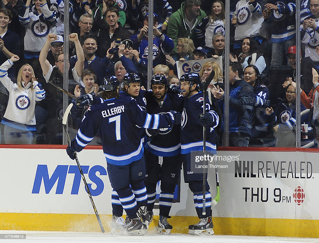 Keaton Ellerby #7, Olli Jokinen #12, Dustin Byfuglien #33 and Eric Tangradi #27 of the Winnipeg Jets celebrate a third period goal against the Ottawa Senators at the MTS Centre on March 8, 2014 in Winnipeg, Manitoba, Canada.