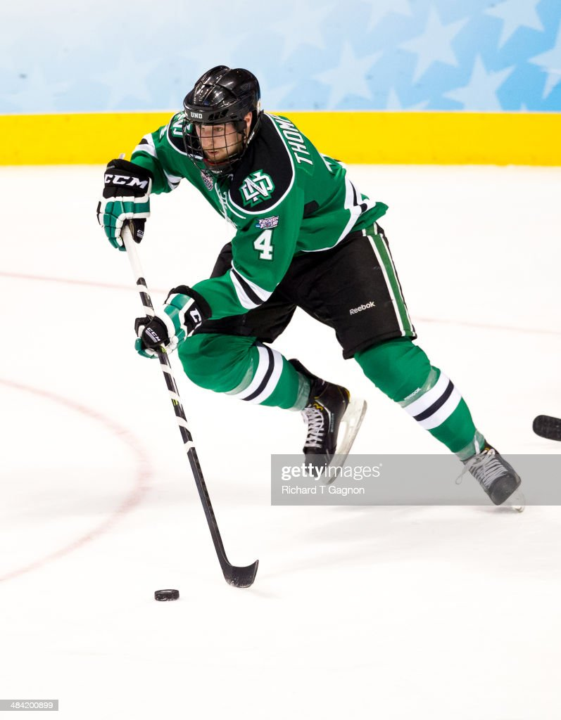 Keaton Thompson of North Dakota controls the puck against the Minnesota Golden Gophers during the NCAA Division I Men's Ice Hockey Frozen Four...
