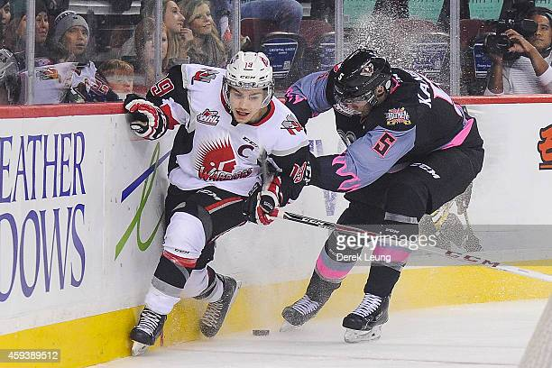 Keegan Kanzig of the Calgary Hitmen checks Brayden Point of the Moose Jaw Warriors during a WHL game at Scotiabank Saddledome on November 21 2014 in...