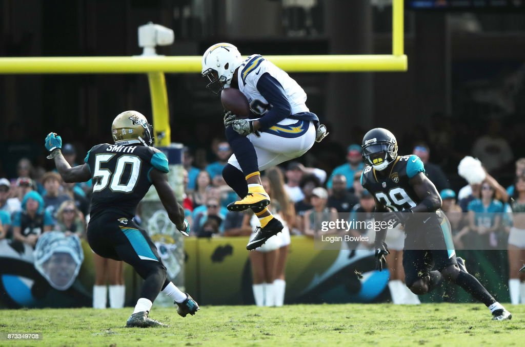 Keenan Allen #13 of the Los Angeles Chargers leaps for the football in between Telvin Smith #50 and Tashaun Gipson #39 of the Jacksonville Jaguars in the second half of their game at EverBank Field on November 12, 2017 in Jacksonville, Florida.