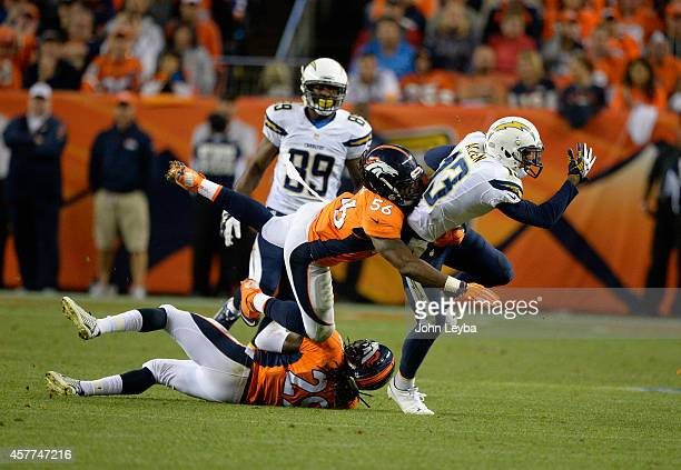 Keenan Allen of the San Diego Chargers leaps over Bradley Roby of the Denver Broncos and is tackled by Nate Irving of the Denver Broncos in the...