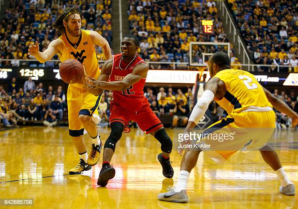 Keenan Evans of the Texas Tech Red Raiders handles the ball between Nathan Adrian and Jevon Carter of the West Virginia Mountaineers at the WVU...
