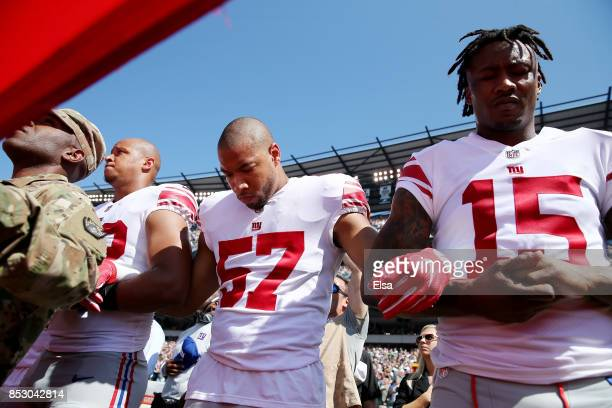 Keenan Robinson and Brandon Marshall of the New York Giants link arms during the national anthem before the game against the Philadelphia Eagles on...